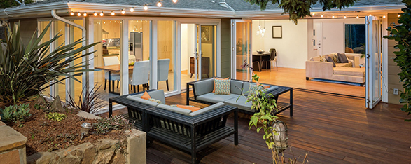 Home with furniture patio / wooden deck at twilight.